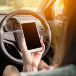 woman holding her cell phone instead of the steering wheel
