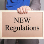 """A pink sign that reads """"new regulations"""" as laws look to improve the current system"""