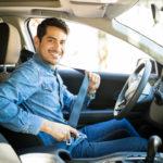 Man sitting in car seat fastening seat belt