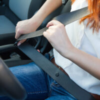 Woman fastens a seat belt. Safe driving concept